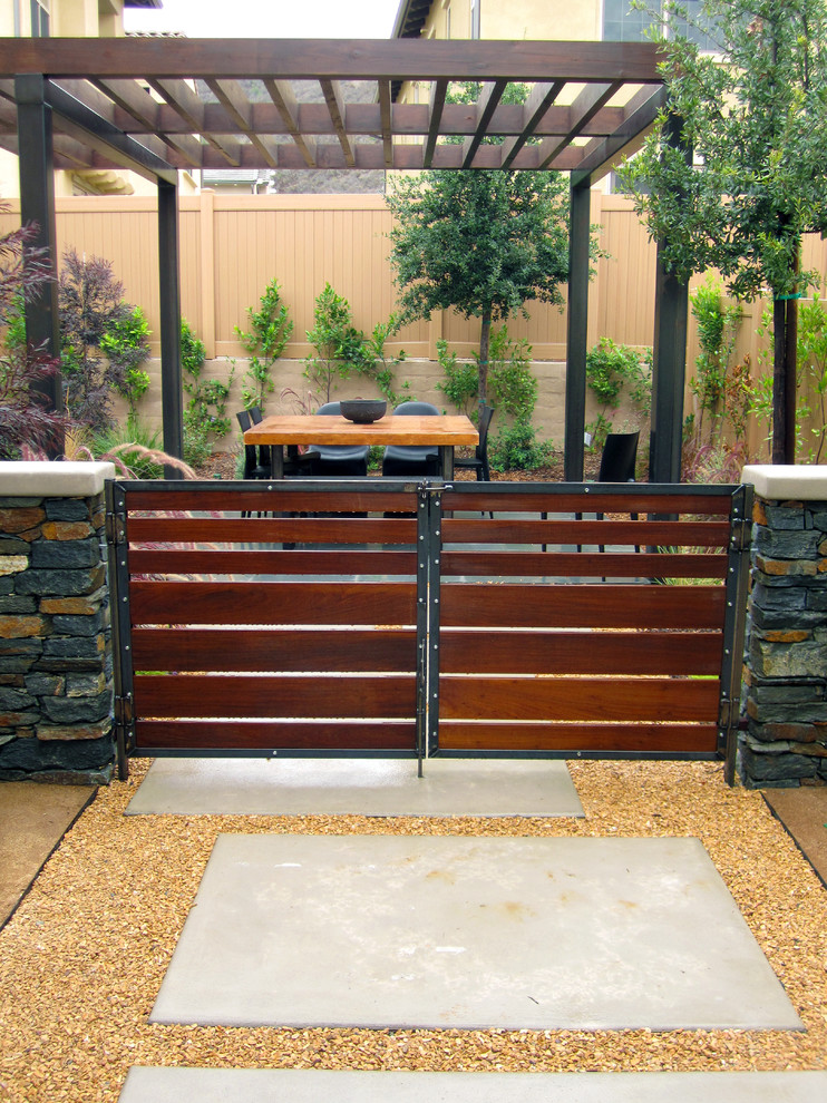 Custom wood gates with steel framing and hardware. Patio cover with outdoor dining area on a blue stone patio.