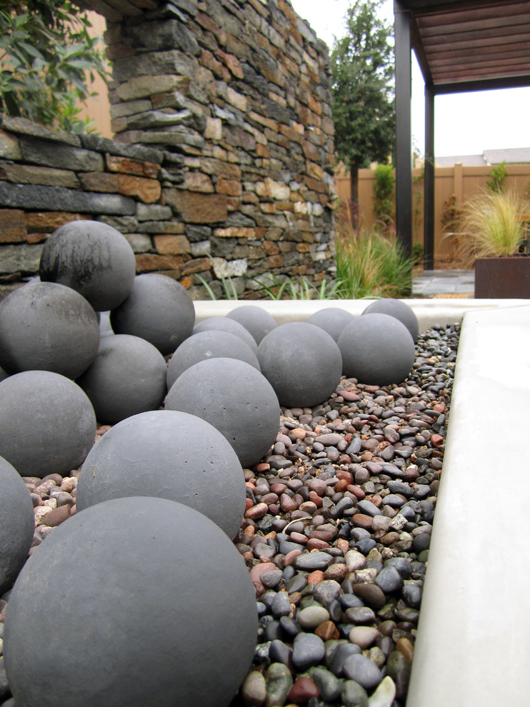 Modern fire pit with fire spheres in decorative gravel with floating accent wall behind.