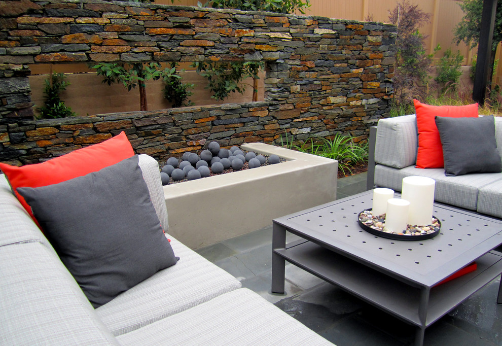 Outdoor seating area with sofas and coffee table adjacent to gas fire pit with floating wall.