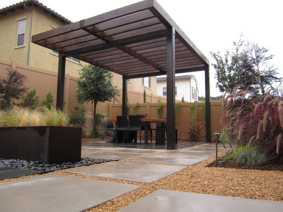 Outdoor dining area with pergola with steel posts and open lattice design. All wood has hidden hardware and semitransparent stain. Modular concrete pads transition through the space with decorative gravel in joints making this a permeable hardscape design. Corten steel planter in Mexican Beach Pebble in the foreground, planted with Stipa tenuissima. Other plants include Pennisetum, Lavenders, Carolina Cherry, Virginia Oak, and other drough tolerant plants.