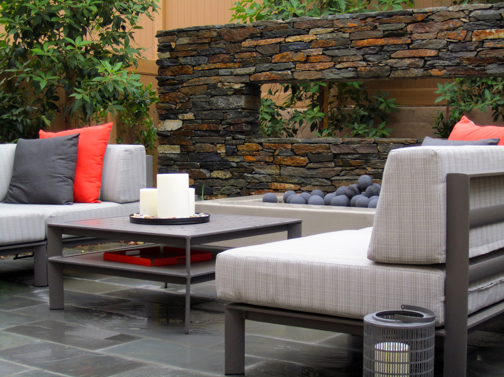 Outdoor fire place and seating area. Black slate used on the ground plan, Bouquet Canyon ledger stone on the floating wall. Brisbane Box as screening tree behind. Dominic Masiello