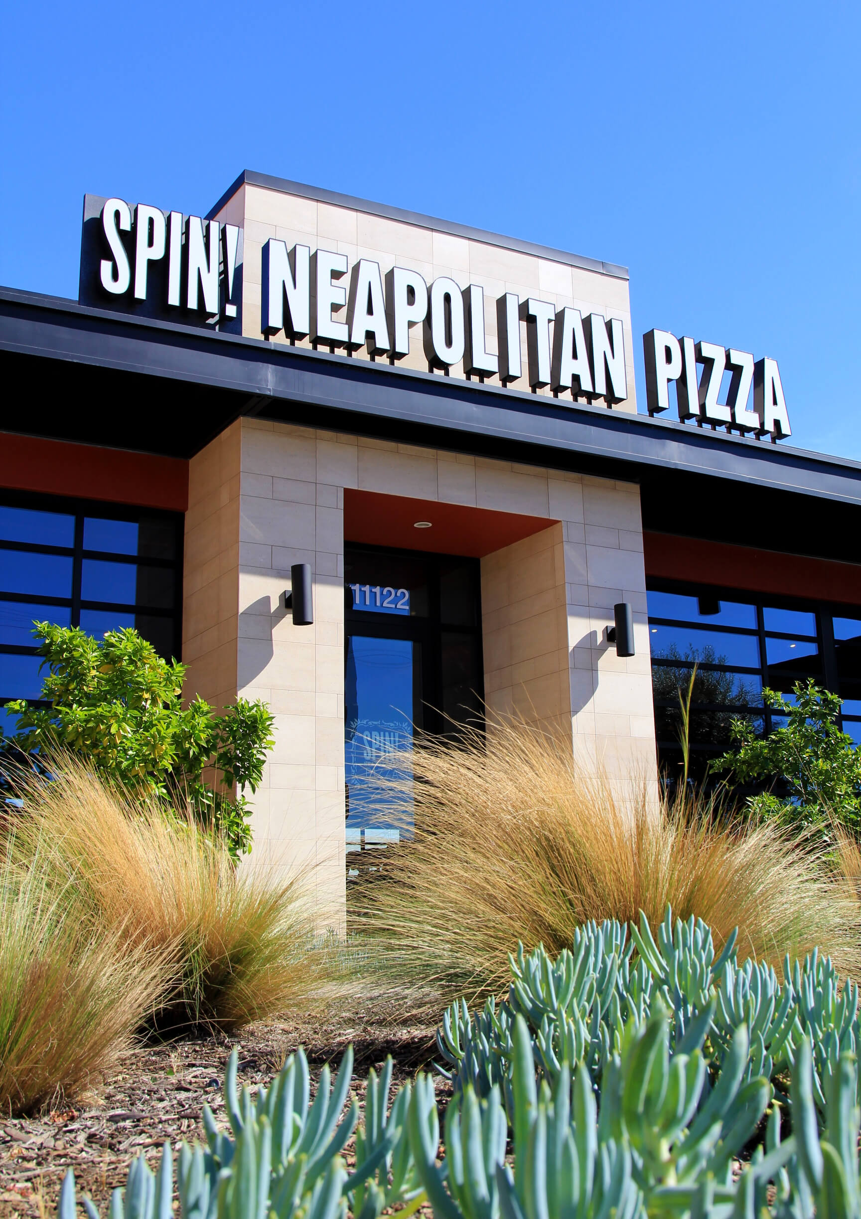 Newly constructed Spin! Pizza in Long Beach, California.  The modern eatery needed a landscape to compliment the architecture with linear grasses, large swatches of bold colored succulents, and field-grown mature Olive trees.