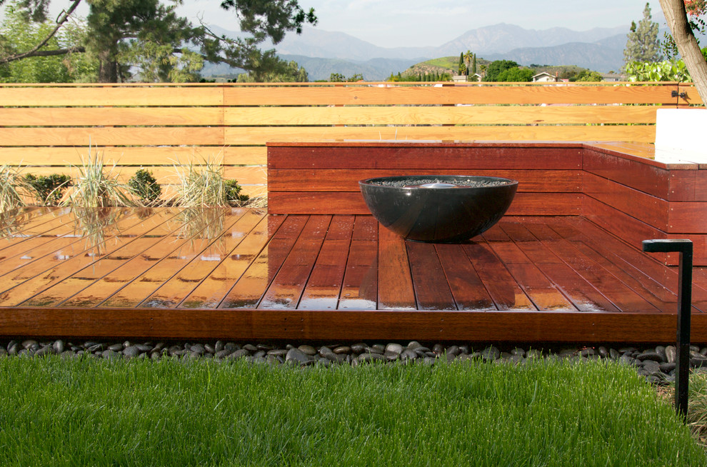 Elevated 'floating deck' with Mangaris wood. Black precast concrete fire bowl surrounded by built-in seating with perimeter fence. Fescue lawn with an accent ribbon of black Mexican beach pebble.