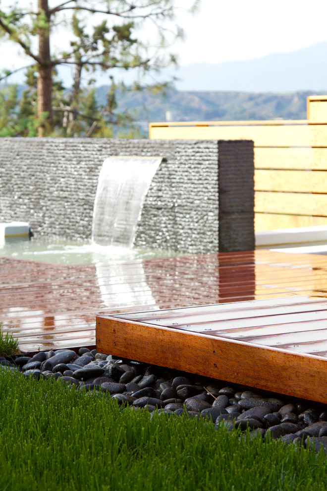 Elevated wood deck surrounded by black Mexican beach pebbles. Water feature with striated granite accent wall spills into a pond basin. Fescue lawn in foreground.
