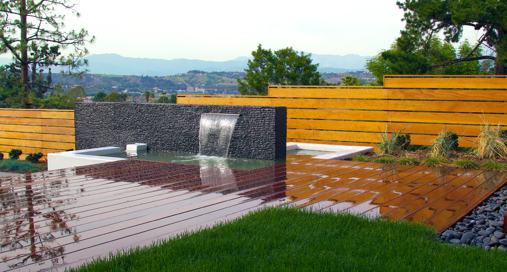 Modern back yard entertainment space with granite accent wall and spillway. Smooth white walls contrast against dark Mangaris wood deck. Fescue lawn in foreground with a ribbon of black Mexican beach pebbles. Space overlooks San Gabriel Valley and hills of Cal Poly Pomona's CLA building.